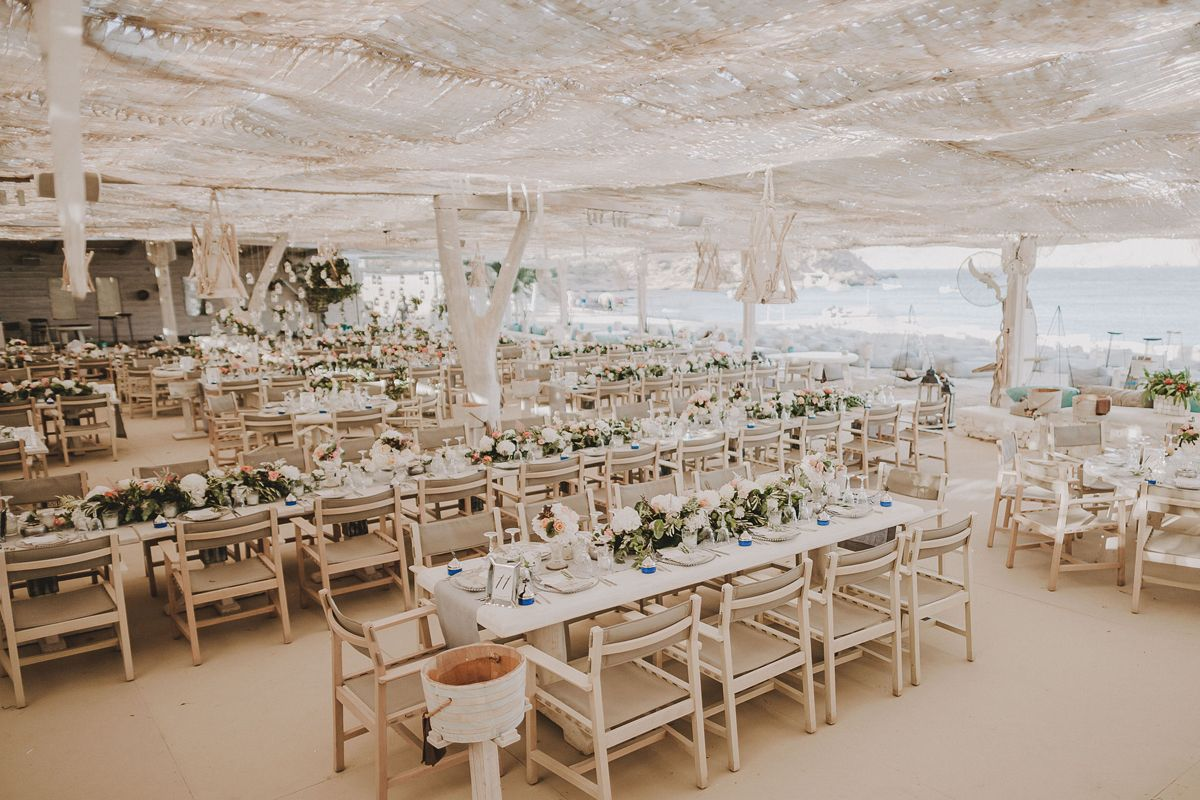 vintage_beach_wedding_flowers_dinner_area_candles_dinnerware_number_mykonos_panormos_deplanv.jpg
